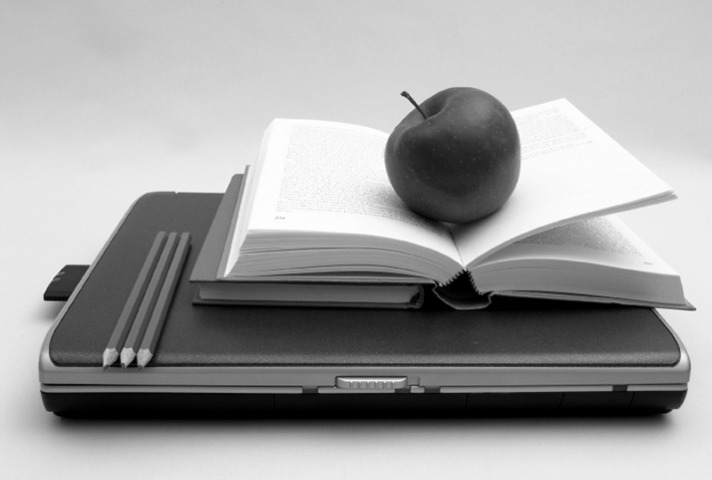 Lunch and Learn - photo of apple placed on top of a book and laptop