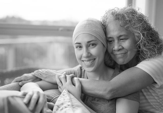Older woman hugging female cancer patient